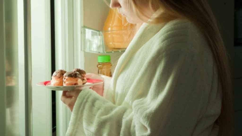Una joven sufriendo un antojo nocturno.