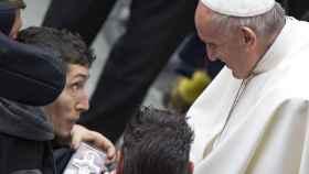 El papa Francisco recibe una cruz como presente tras su tradicional audiencia general de los miércoles.