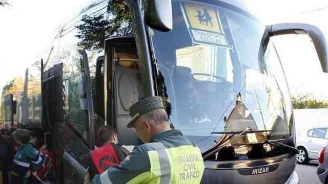 Un guardia civil revisa los papeles de un autobús de transporte escolar en Torrejón de la Calzada (Madrid).