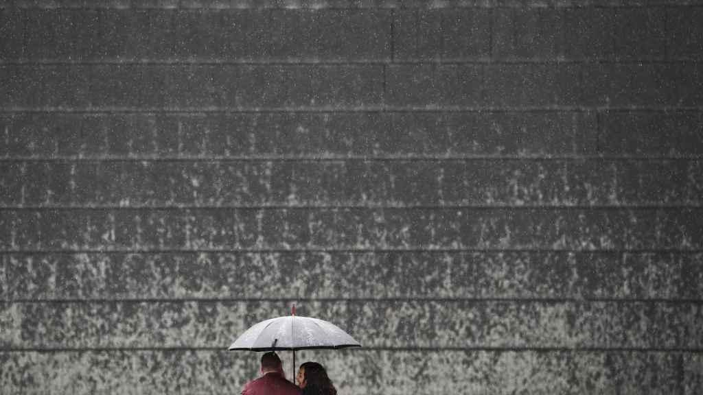 Una pareja se protege de la lluvia en Pamplona.