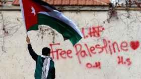 Un manifestante con una bandera de palestina.