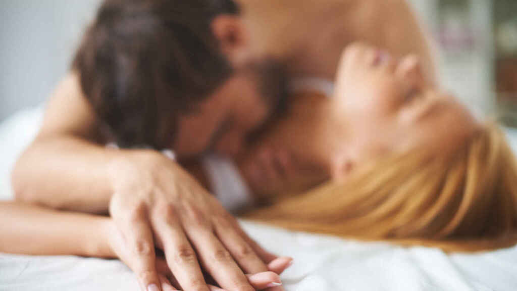 Una pareja entreteniéndose bien bajo las sábanas.