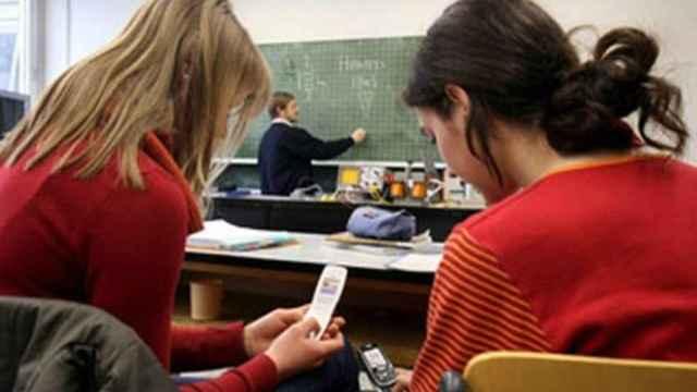 Niñas  usando el móvil en clase.