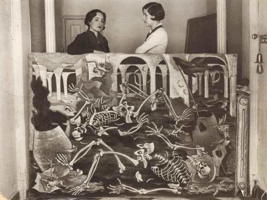 Maruja Mallo con Josefina Carabias, apoyadas sobre su óleo 'Antro de fósiles'.  Guillermo de Osma.