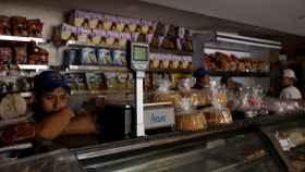 Un vendedor espera en la oscuridad dentro de una panadería, en Caracas.