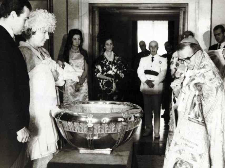 La reina Sofía, Carmen Polo, Franco y el rey Juan Carlos (al fondo a la derecha) en el bautizo de la infanta Elena.