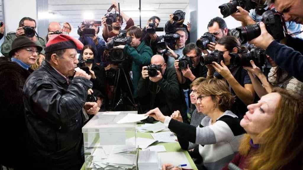 Un ciudadano con la típica barretina catalana, ejerce su derecho al voto en un colegio electoral.