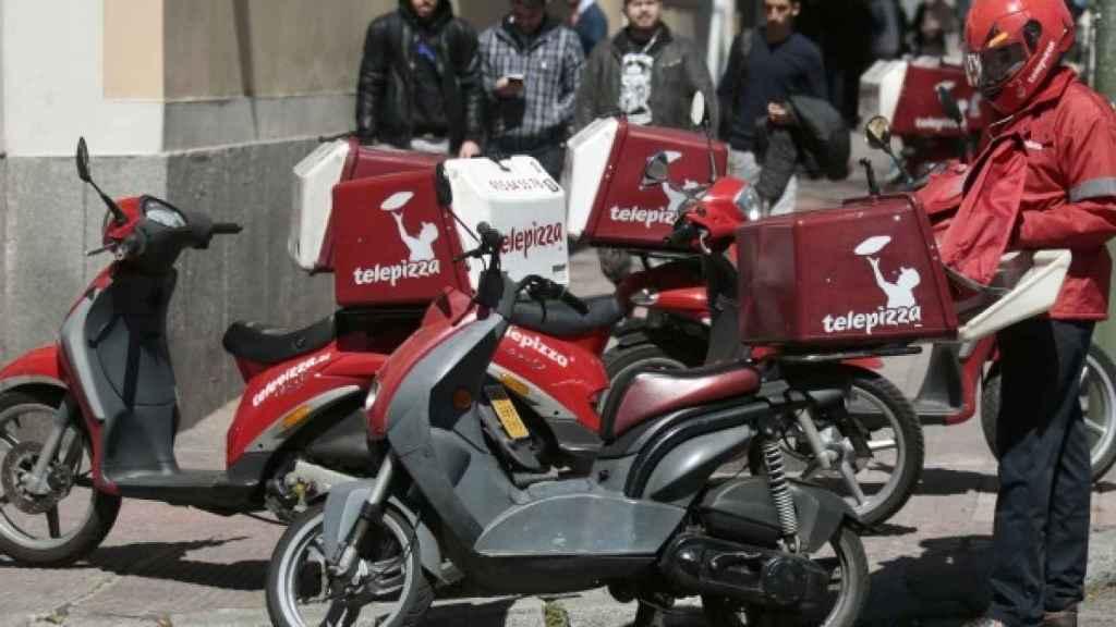 Un repartidor a punto de coger su moto, en una imagen de archivo.