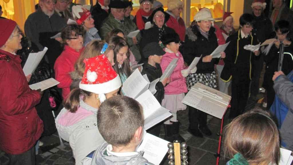 Un grupo de personas cantan villancicos navideños.
