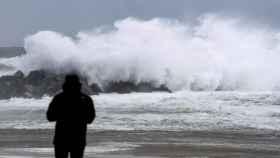 Un hombre observa un ola en el espigón del Kursaal, en San Sebastián