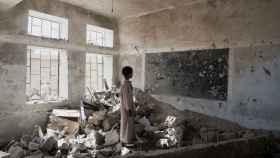 Un joven estudiante contempla las ruinas de lo que fue su escuela en Saada, Yemen