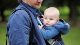 Un padre pasea a su bebe recién nacido.