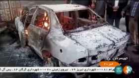 Las personas se paran cerca de un automóvil en llamas en Zanjan, Irán.