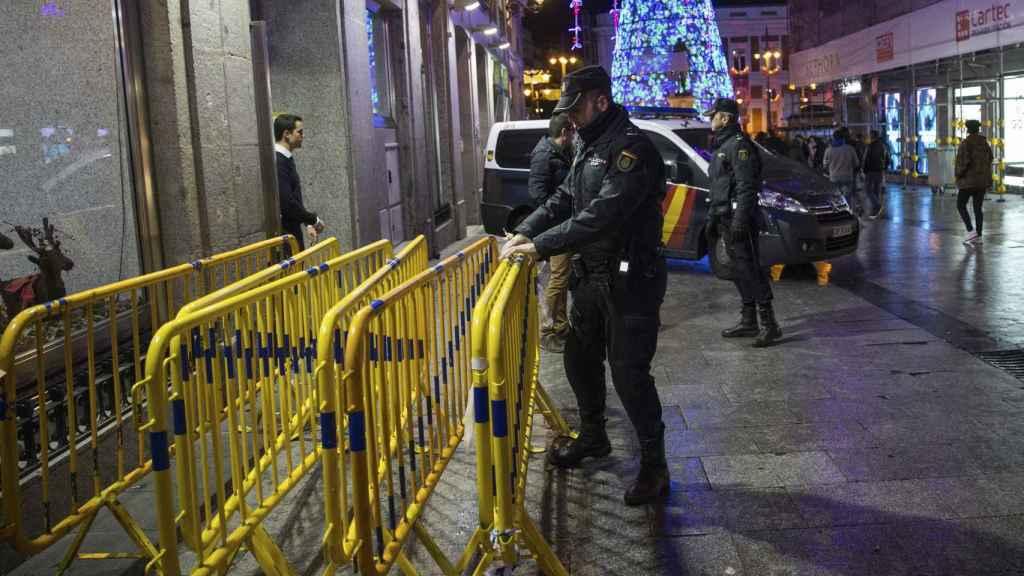 La policía procediendo a instalar vallas en una calle de Madrid.