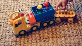 Un niño juega con un camión de juguete.