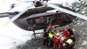 Fotografía cedida por la Agencia Andina, del rescate de una de las víctima del autobús siniestrado.