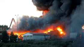 Los Bomberos de Gijón trabajan en las labores de extinción de un incendio en un empresa de desguaces.