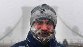 Un peatón camina sobre la nieve cruzando el puente de Brooklyn, en la ciudad de Nueva York.