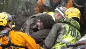 Una mujer es rescatada por los bomberos en Montecito, California.