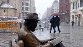 En primer plano, una escultura en León sufriendo una copiosa nevada.
