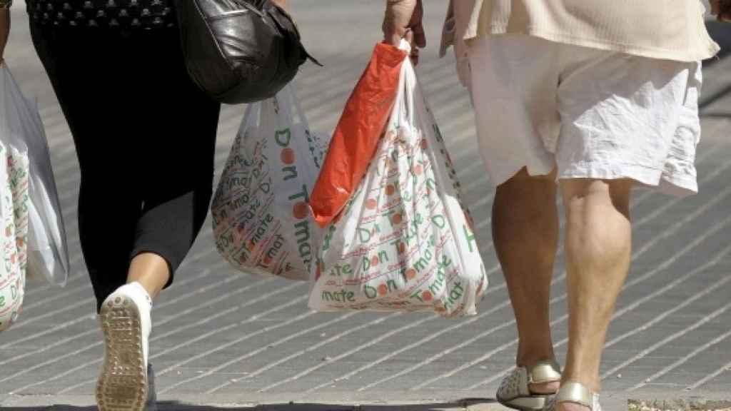 Dos mujeres con bolsas de plástico tras realizar unas compras, en una imagen de archivo.