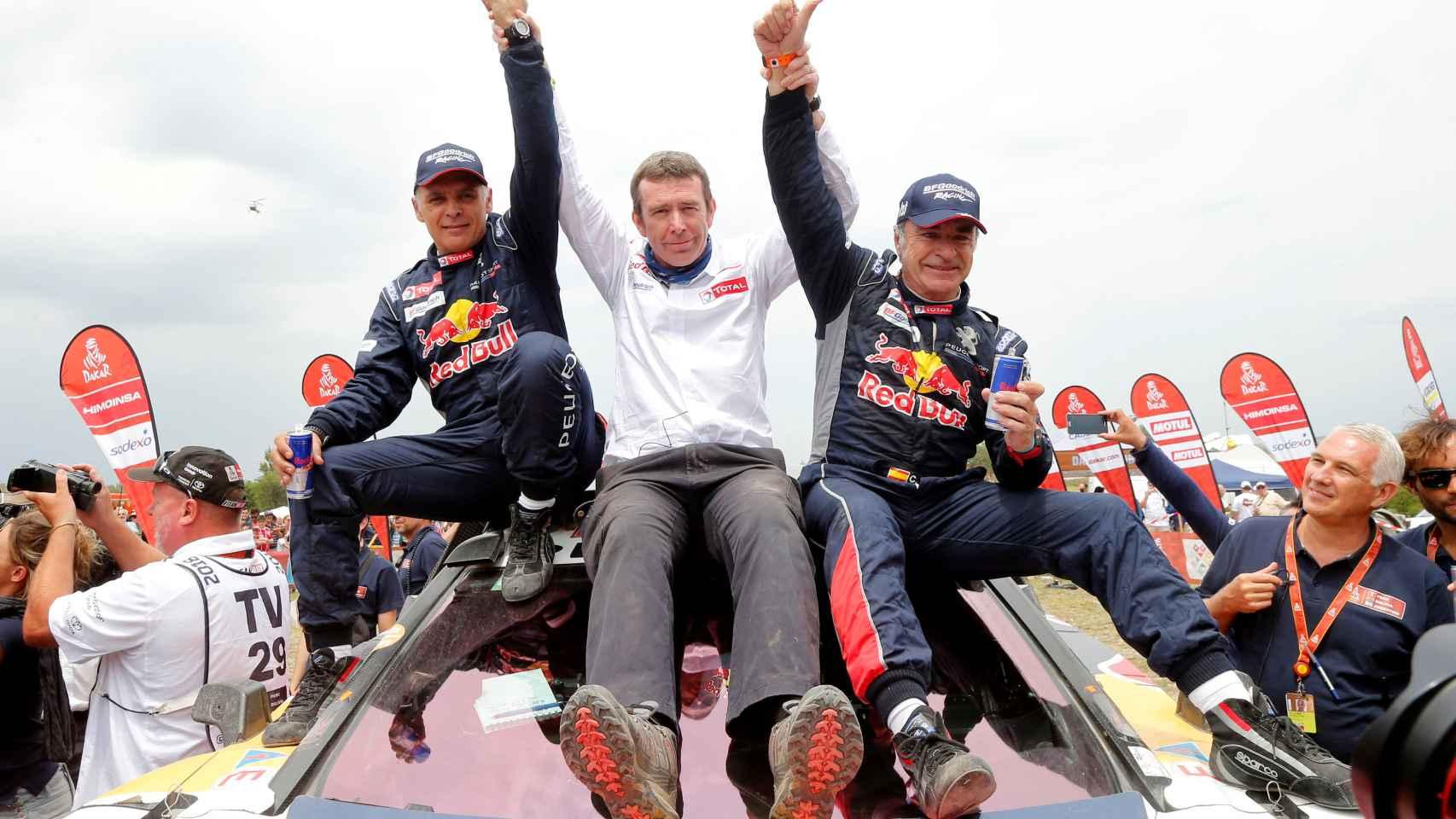 Sainz celebra la victoria con su copiloto Lucas Cruz y el jefe del equipo Reanult.
