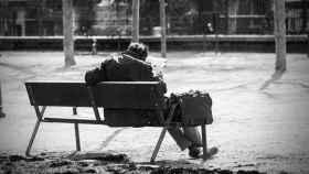 Un anciano lee solo el periódico en el banco de un parque.