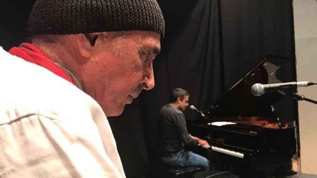 Guix toca el piano ante la mirada de Lluís Llach.