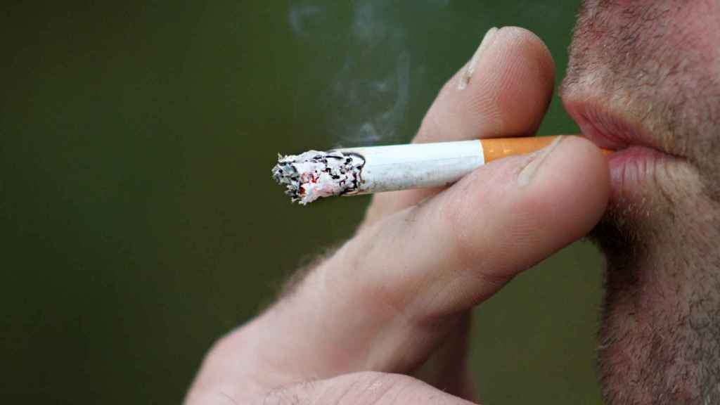 Un hombre disfrutando de su único cigarrillo del día.