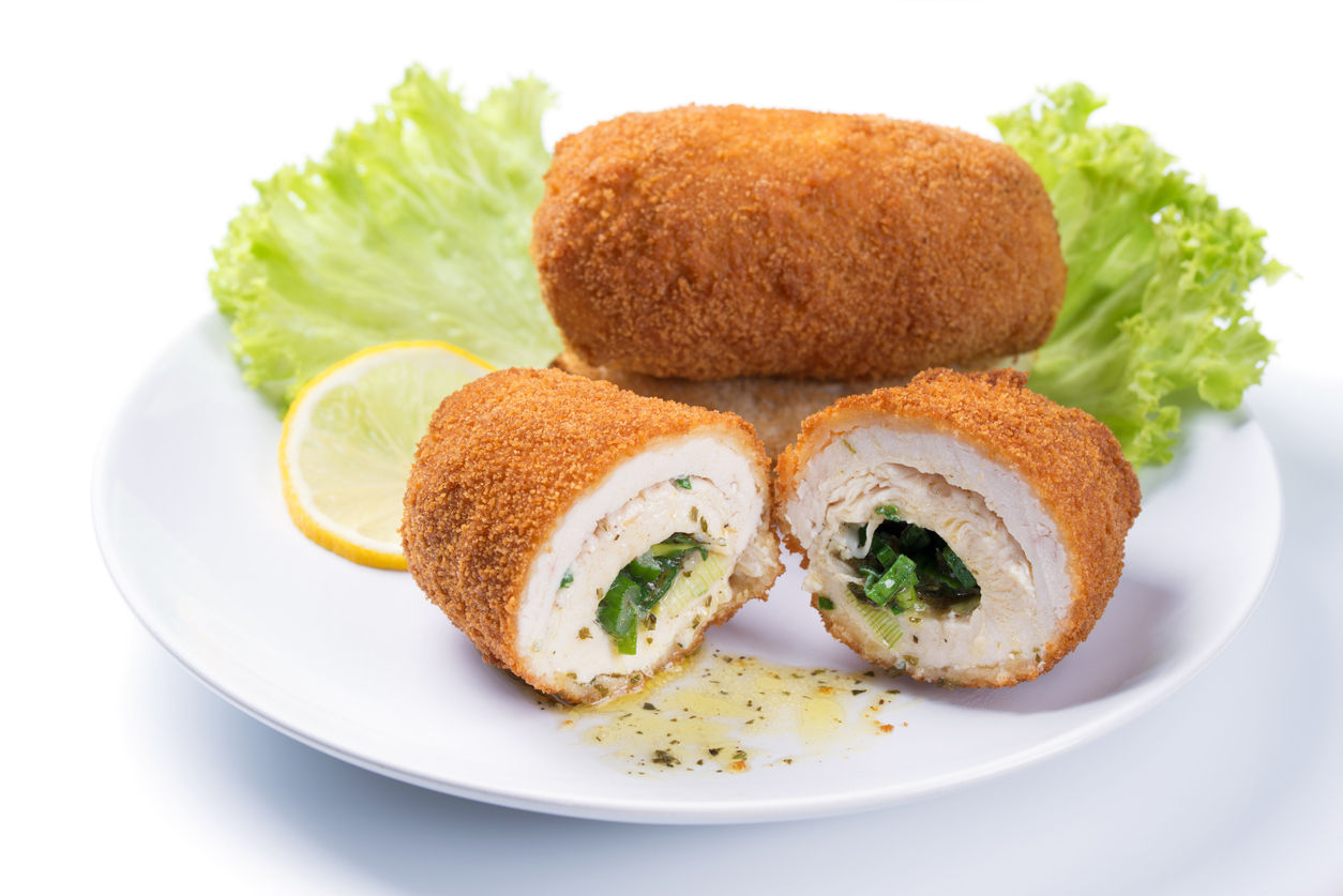 Chicken Kiev cutlet with green salad and lemon slice on a plate, white background