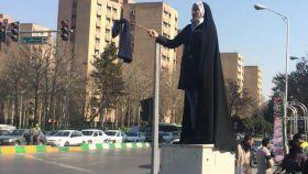Una de las mujeres que ha protestado subida a una caja de la luz contra el chador.