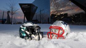 Exterior del US Bank Stadium, con los cascos de Patriots y Eagles sobre la nieve.