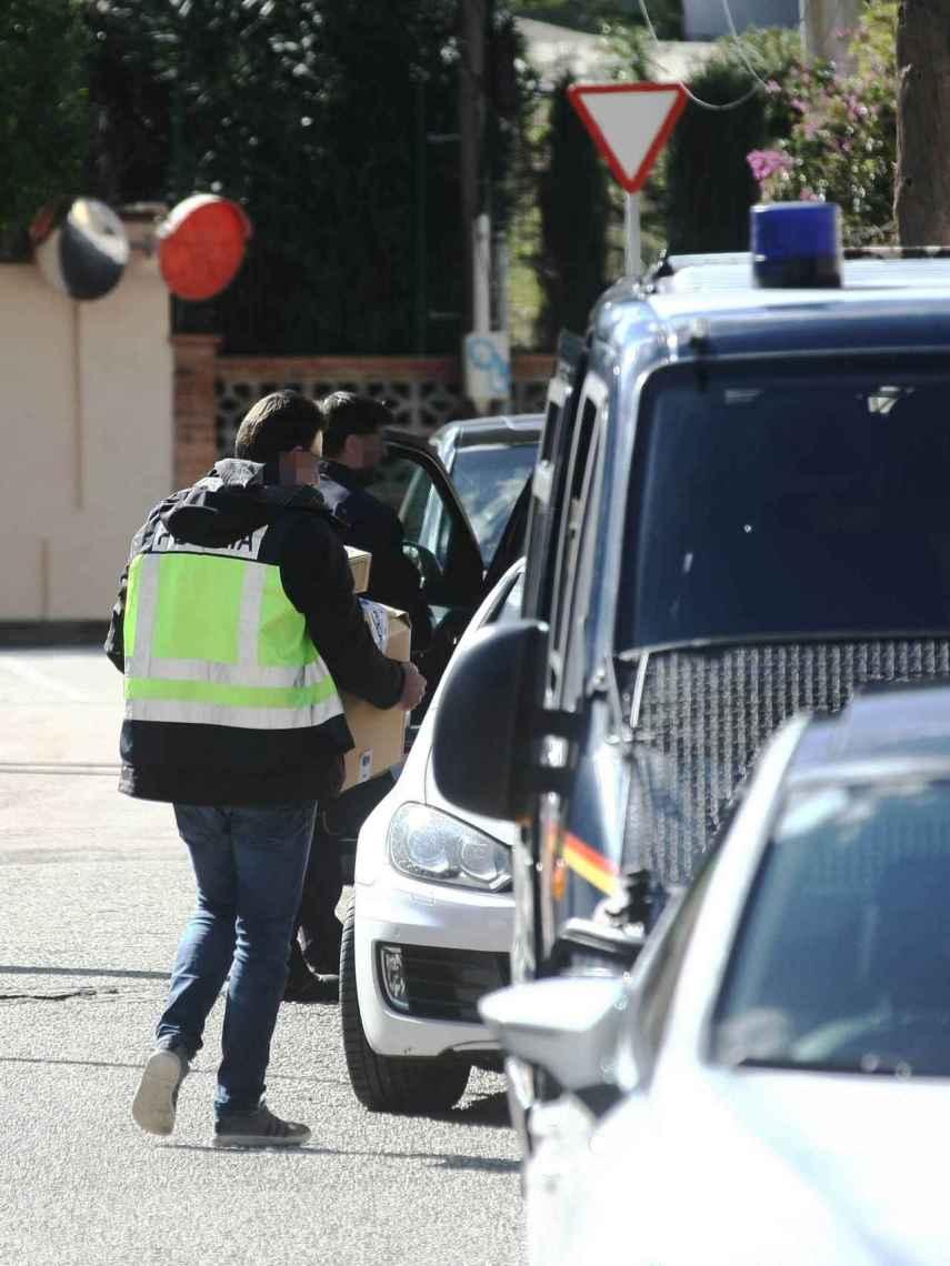 Agentes sacan cajas de la vivienda registrada en la urbanización Colonia San Miguel de la localidad gaditana de Algeciras.