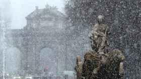 Vista de la Cibeles y la Puerta de Alcalá durante la nevada en Madrid.