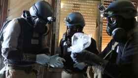 Expertos de la ONU sostienen un recipiente de plástico que contiene material químico.