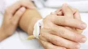 Una persona posa su brazo sobre un enfermo que se encuentra ingresado.