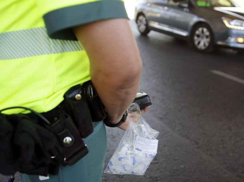 Un agente de la Guardia Civil sostiene una bolsa con boquillas para el control de alcolhemia y drogas.