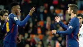 Yerry Mina y Piqué se saludan en un cambio en Mestalla.