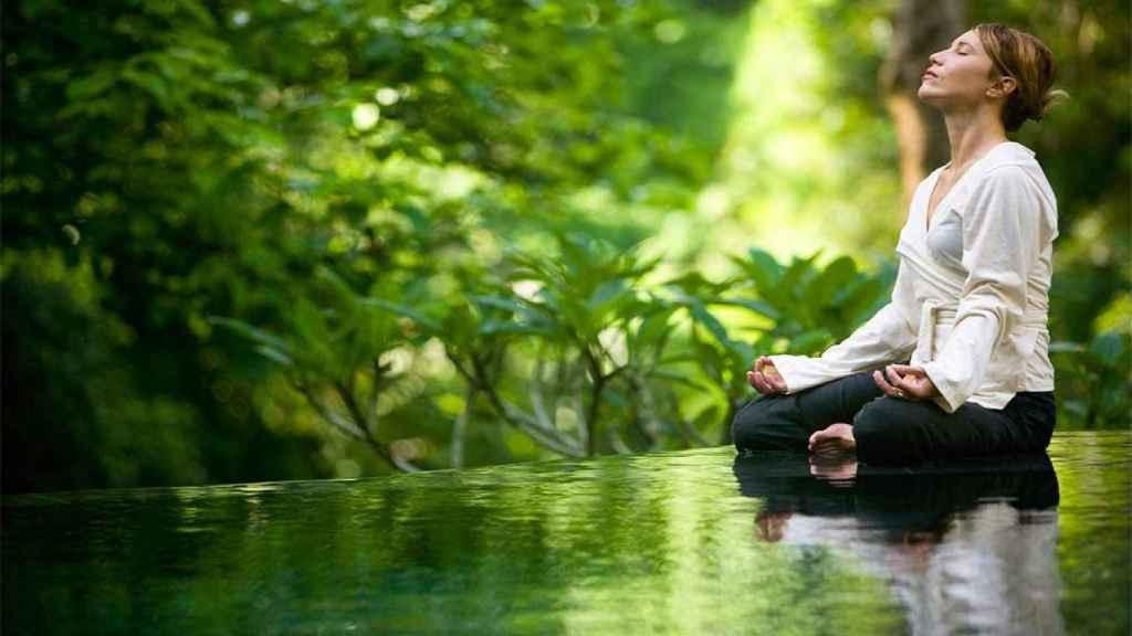 Una mujer medita con los ojos cerrados.