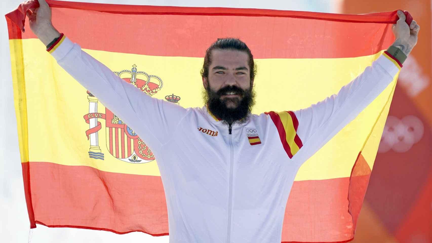 Regino Hernández, feliz, con la bandera de España tras ganar un bronce en los Juegos Olímpicos de invierno.