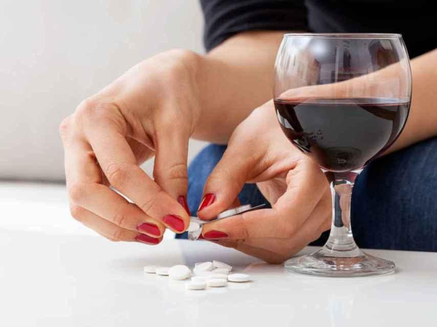 Una persona dispuesta a tomarse una copita de vino junto con algunos medicamentos.