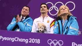 Javier Fernández, con sus entrenadores esperando la nota del programa corto y con un peluche en sus brazos.