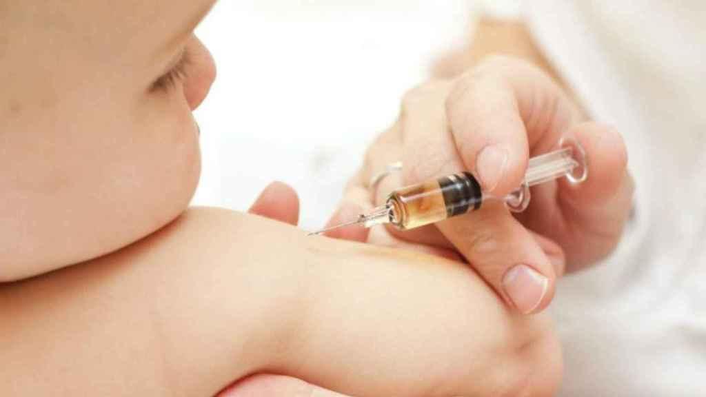 Un médico vacuna a un niño pequeño contra el sarampión.