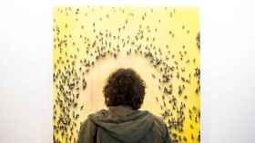 Un visitante en la feria ARCO 2018 observando un cuadro de Juan Genovés.