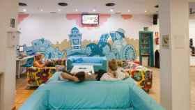 Varios turistas descansan en la sala común de un hostel.