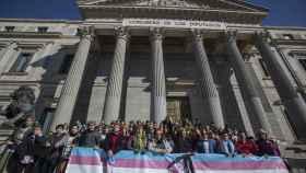 Representantes del colectivo trans junto a políticos de Podemos a las puertas del Congreso de los Diputados