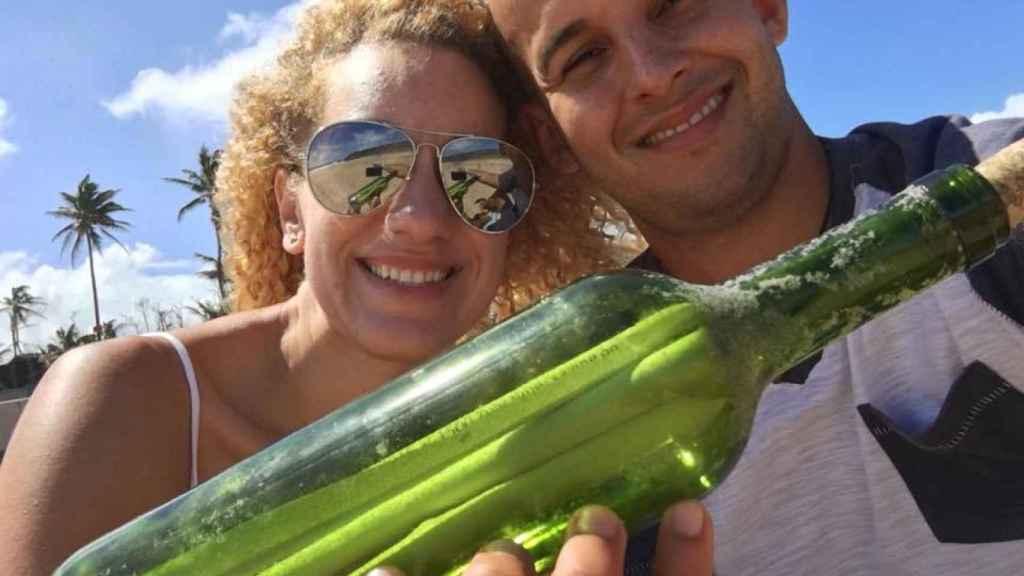 La pareja puertorriqueña sujetando la botella con el mensaje en su interior
