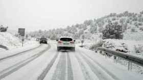 Distintos vehículos circulan por una carretera cubierta de nieve.