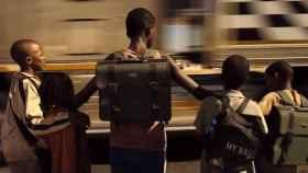 Niños ven pasar un camión de camino al colegio.