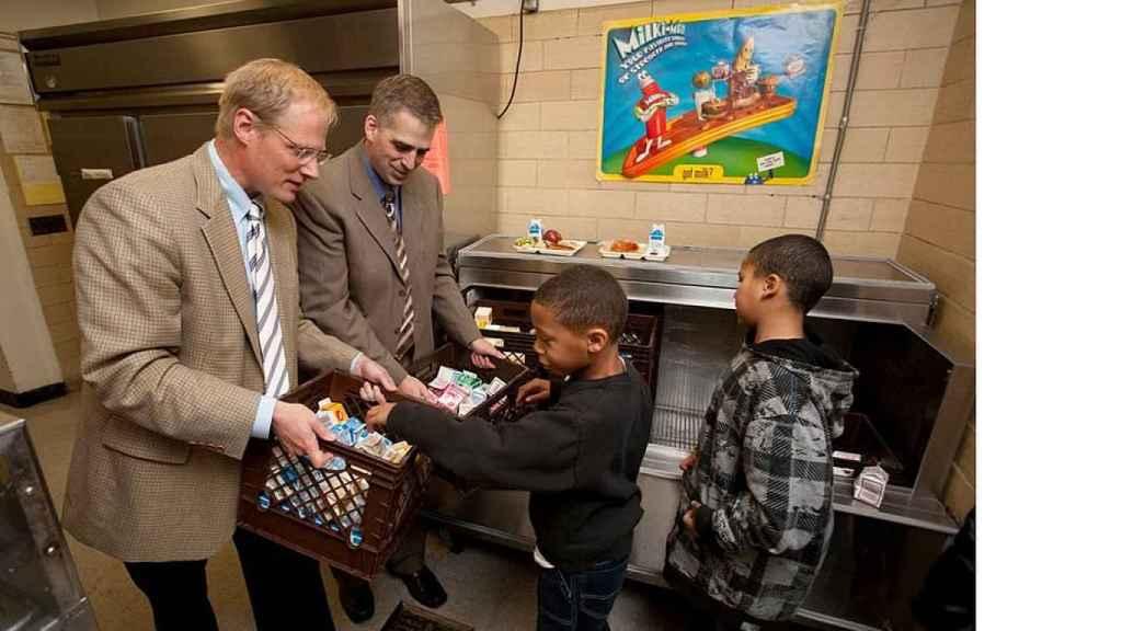 Brian Wansink (a la izquierda) entrega alimentos a unos niños
